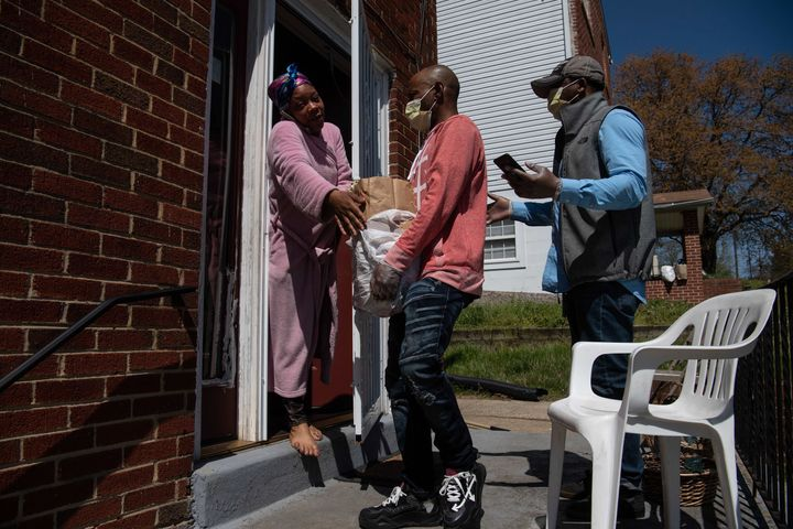 Volunteers deliver groceries to a woman in Washington, D.C., on April 6 amid the coronavirus pandemic. They knew where to go thanks to a mutual aid network set up in the U.S. capital to get help to poor and underserved communities at risk of the coronavirus.