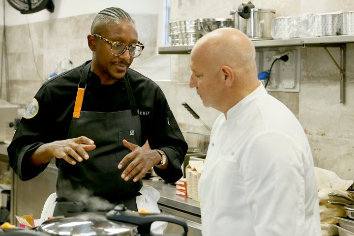 "Gregory Gourdet (left) speaks with judge Tom Colicchio during an episode of the Bravo series ""Top Chef."""