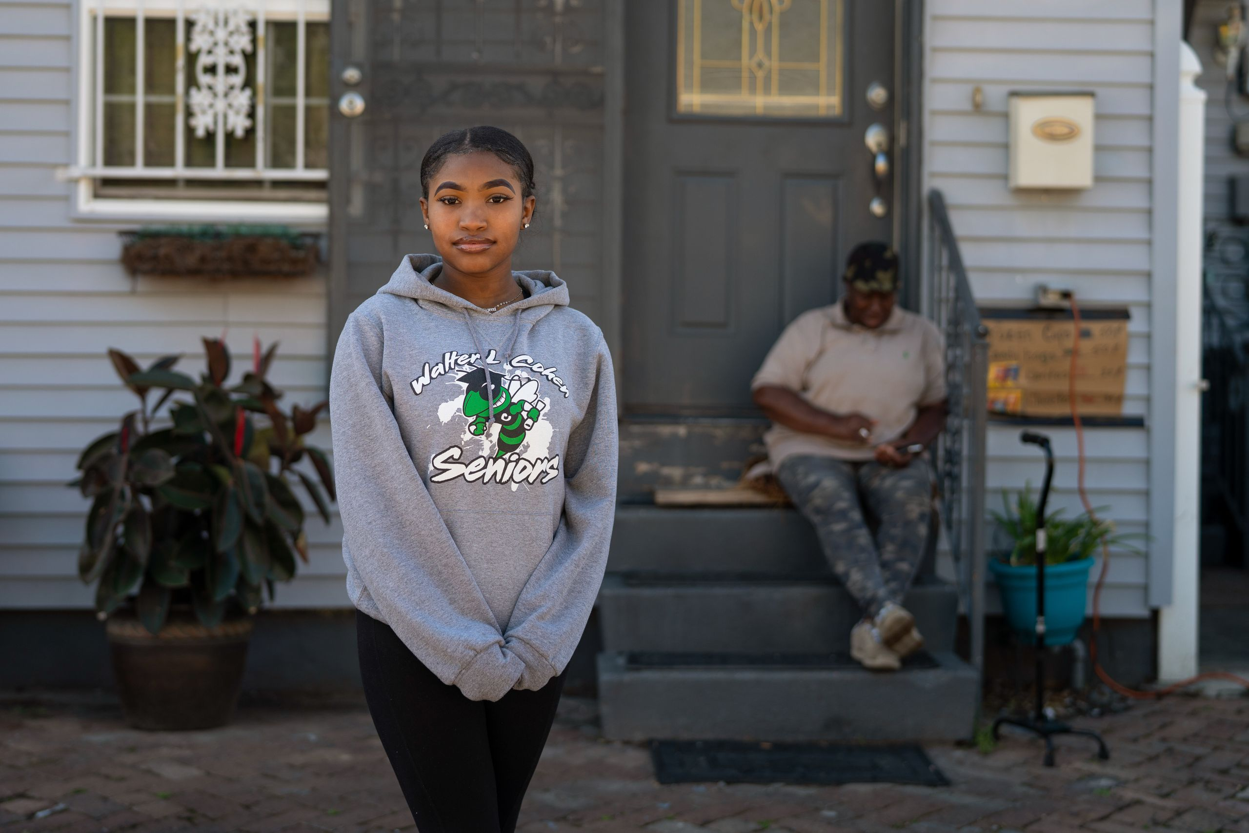 Satoriya Lambert stands in front of her home where she lives with her grandmother, Ether Bullock, 70, a retired teacher, who