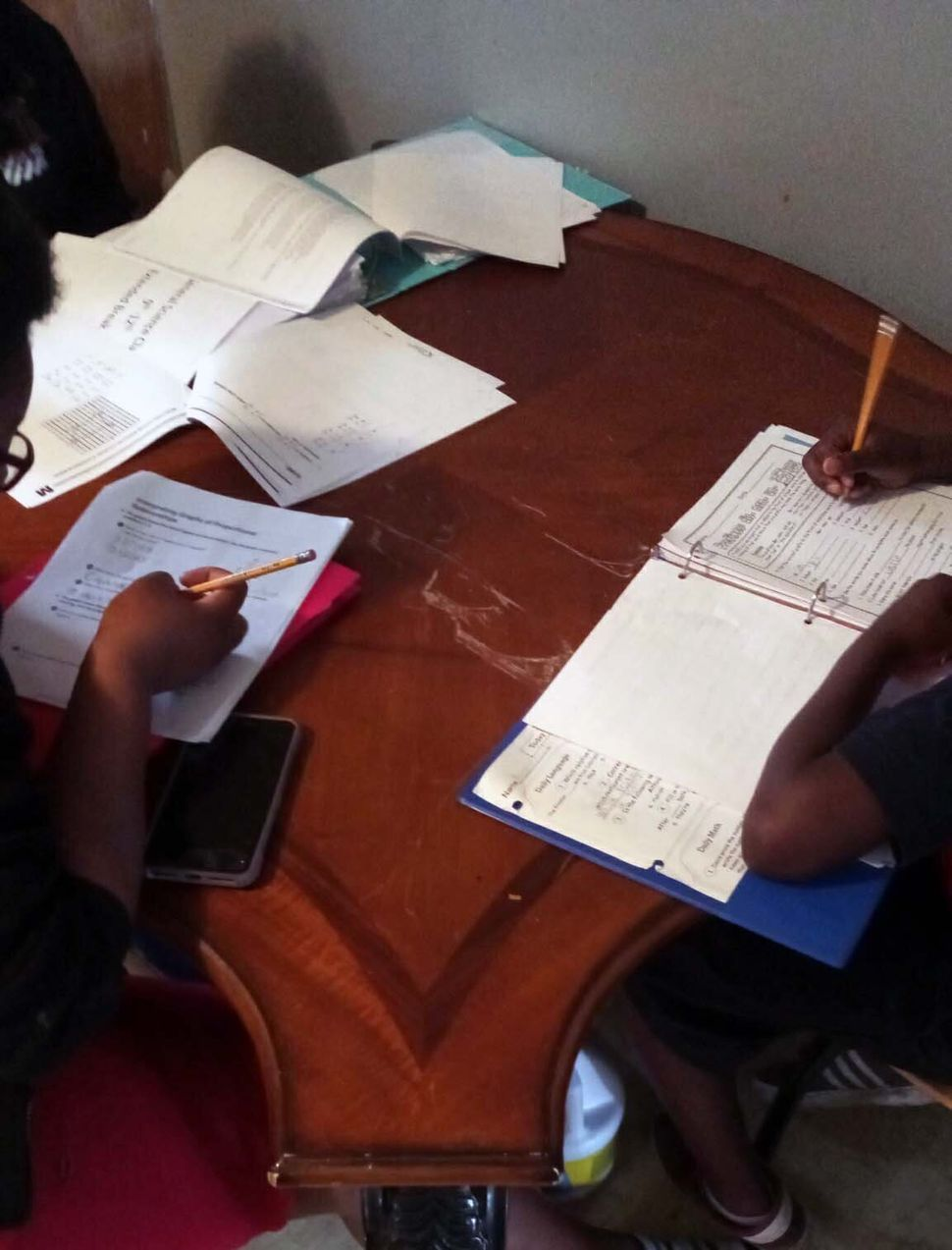 Amareon, right, and his sister Jakayla work on assignments picked up from their local school district. Their family does not