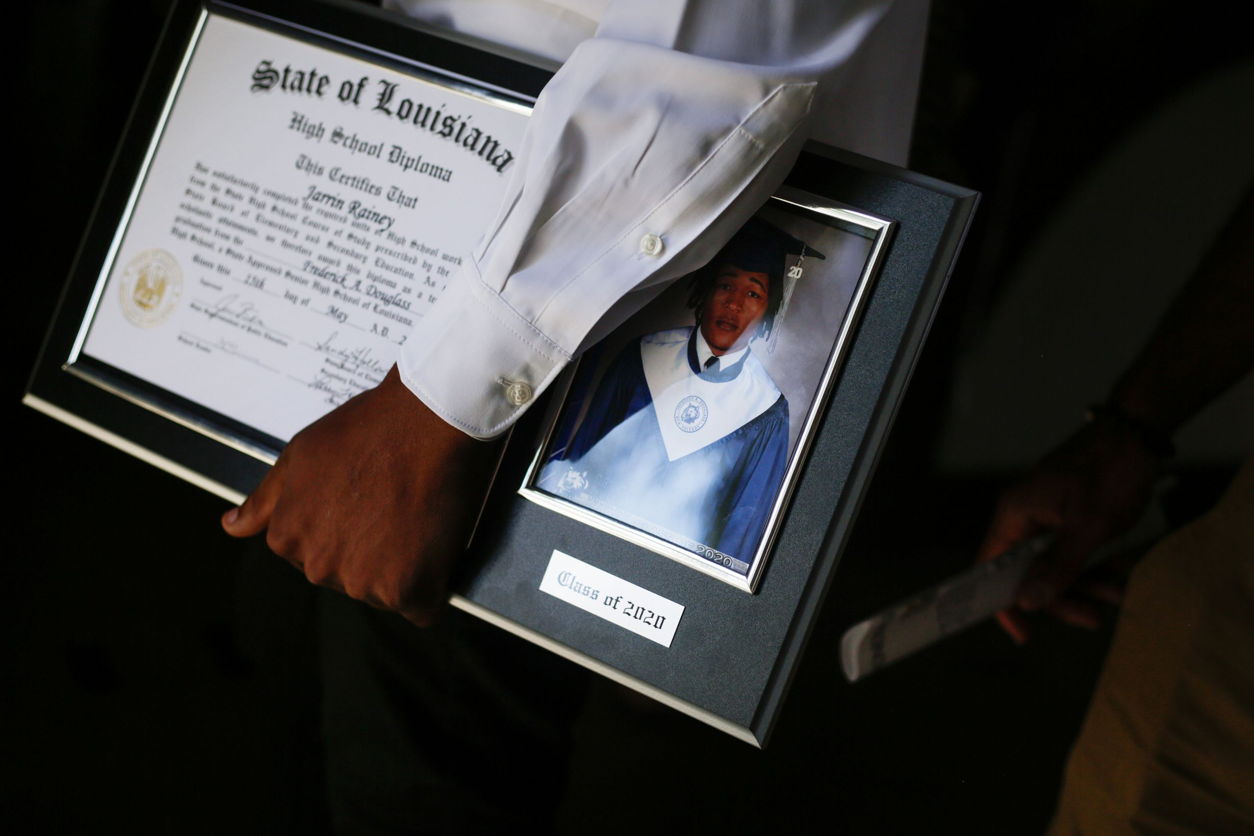 Jarrin Rainey holds his diploma and senior picture plaque after his graduation ceremony at Frederick Douglass High School in