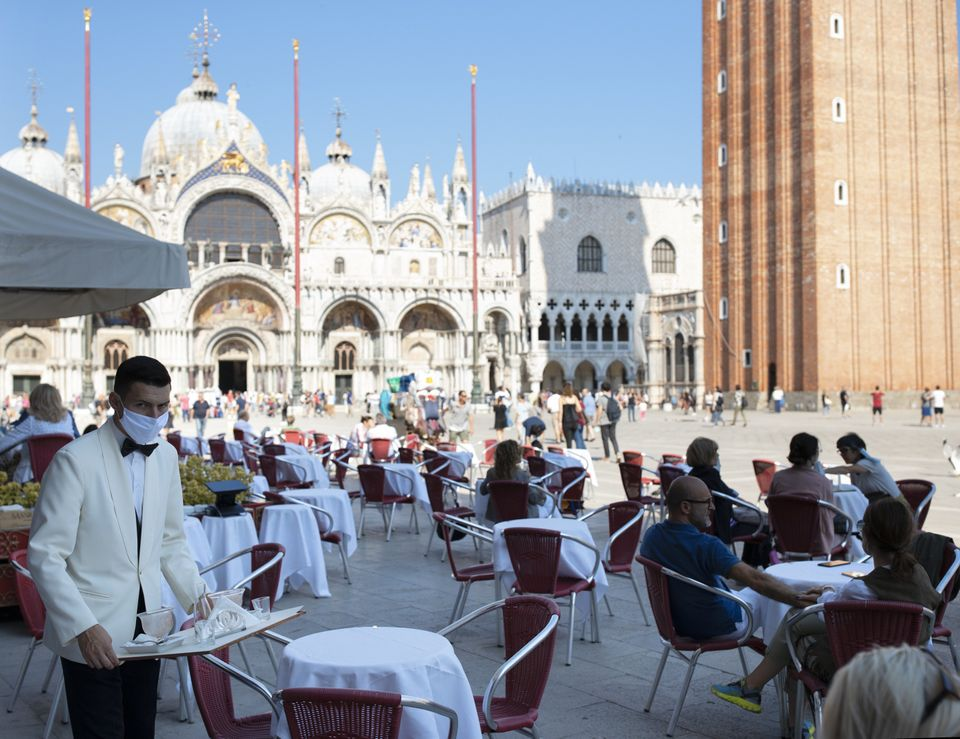 Waiters wearing protective face masks work on the patio facing the Piazza San Marco in Venice, Italy,...