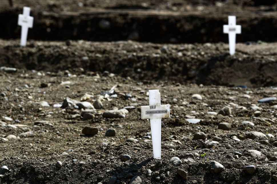 At the Maggiore cemetery in Milan, graves of unclaimed coronavirus victims are marked with a simple plastic cross, April 23, 2020.
