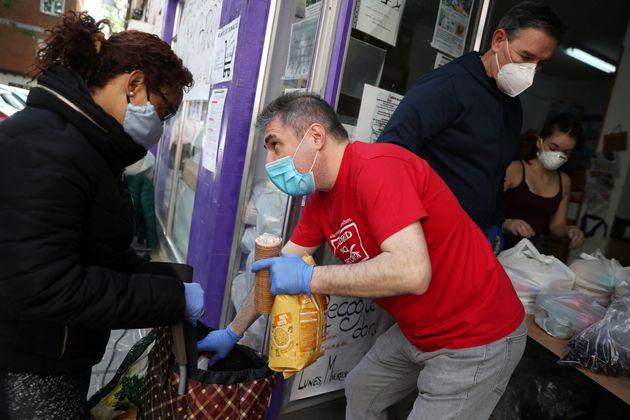 Una mujer recibe comida de unos voluntarios de la asociación de vecinos Parque Aluche, en Madrid,...