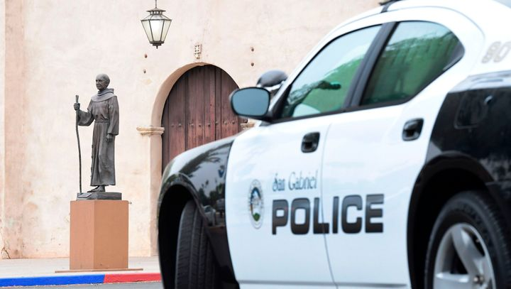 A police vehicle parks near a statue of Junipero Serra in front of the San Gabriel Mission in San Gabriel, California, on Sun