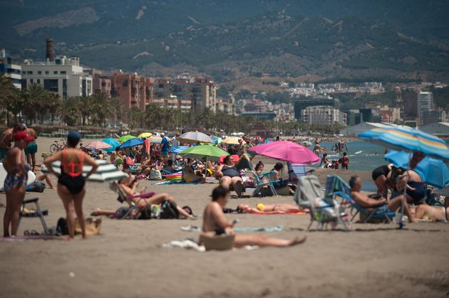 People sunbathing at Misericordia beach in Malaga, Spain - a popular destination for