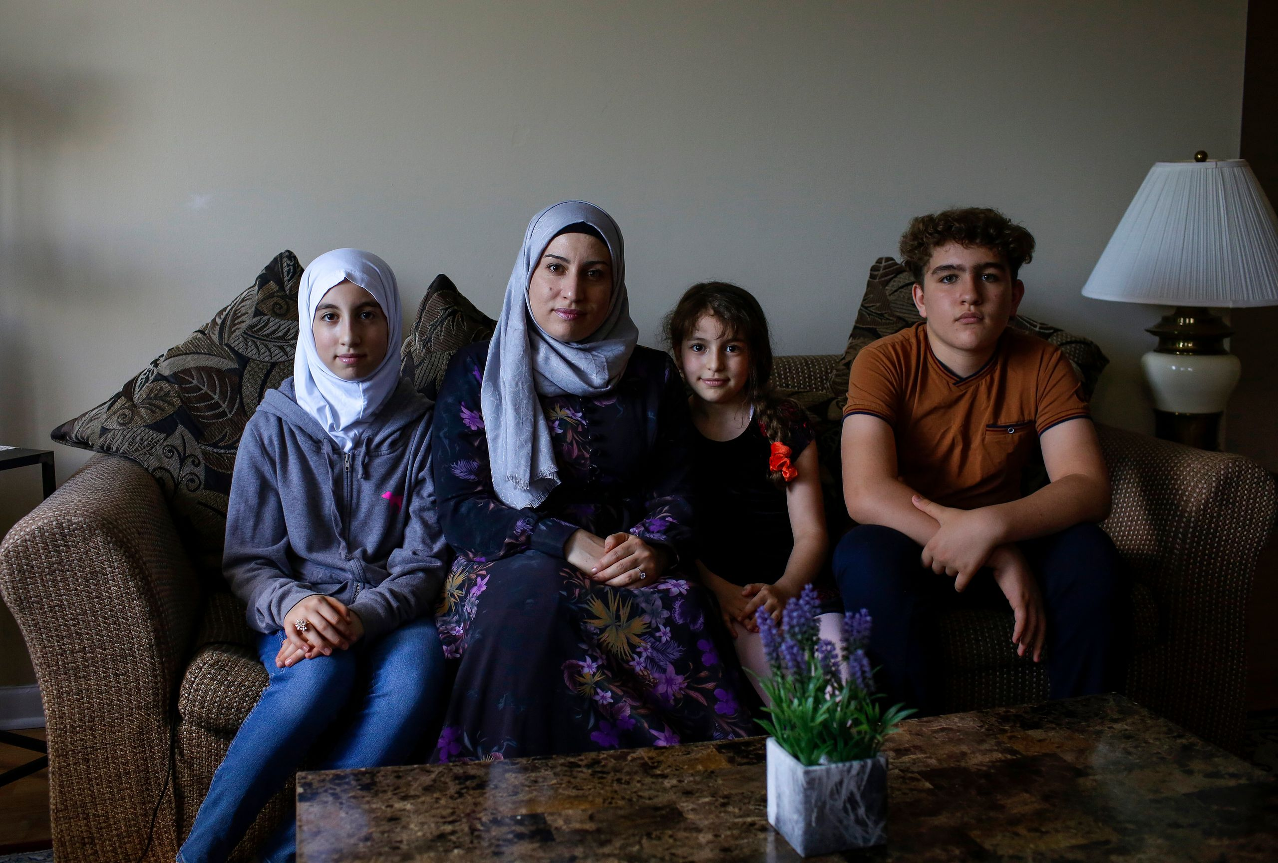 Mohamed Almadani (far right) is a faster reader in English, and often reads aloud for his mother, Nawar Almadani (second from