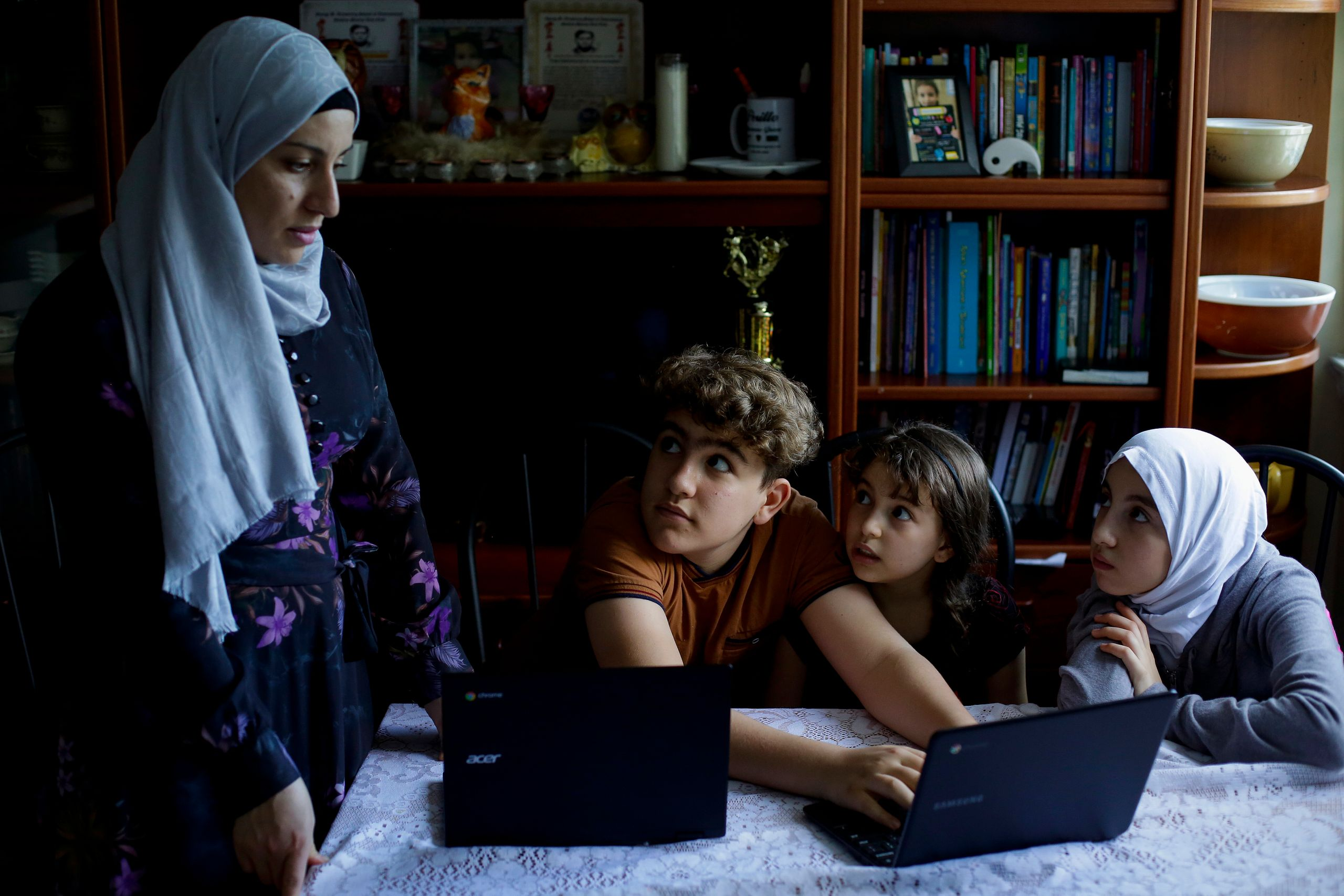 Nawar Almadani, left, watches as her kids Mohamed, Esraaand Baianwork on their computers at their apartment durin