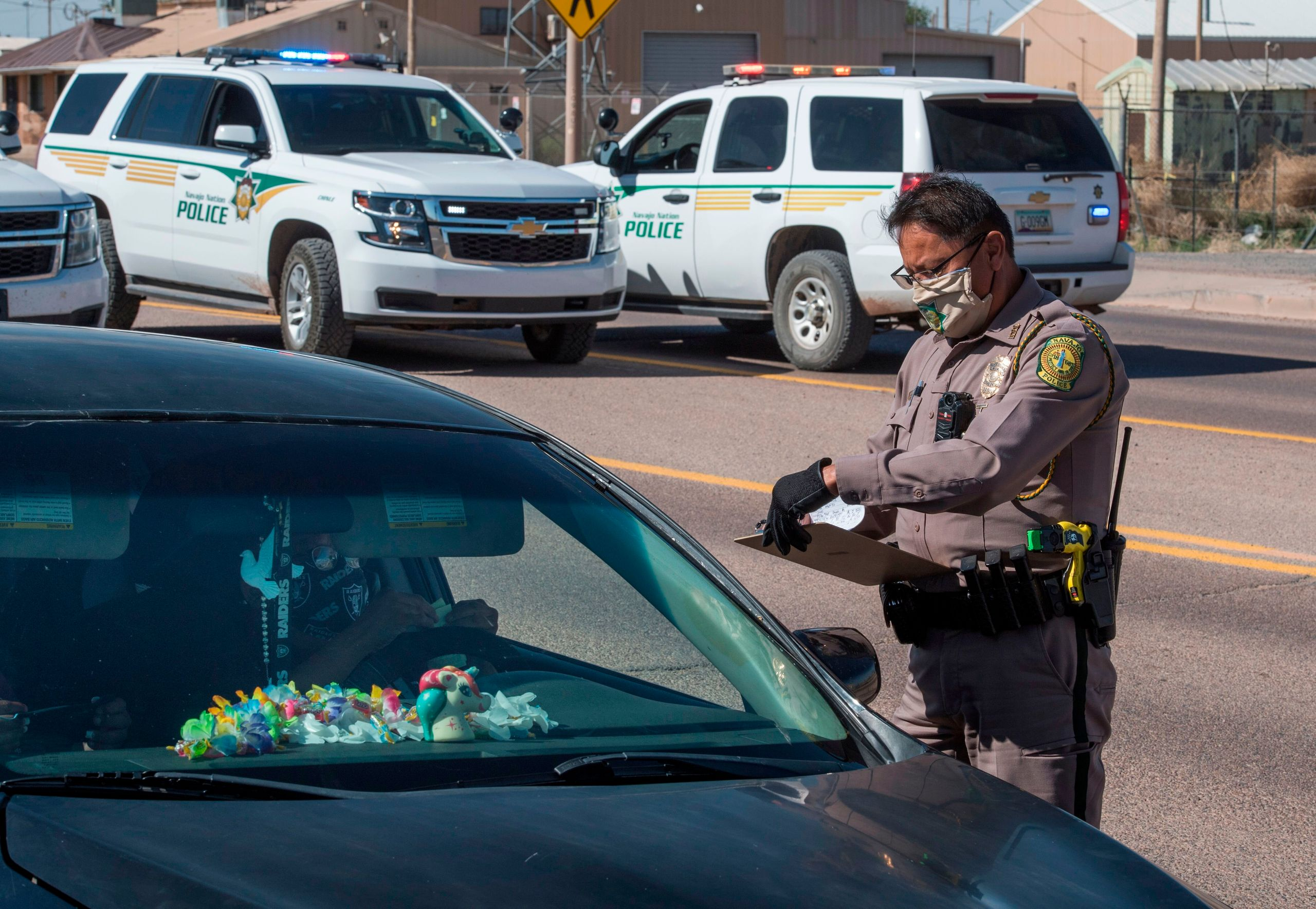 A Navajo Nation police officer issues a fine to a driver who ignored the 57-hour curfew imposed to try to stop the spread of