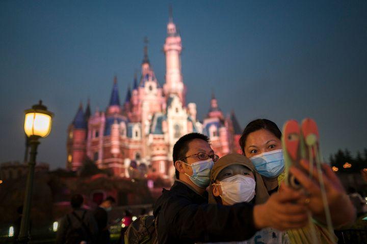 Pessoas de máscara visitam a Disneylândia de Xangai após sua reabertura em 11 de maio de 2020.