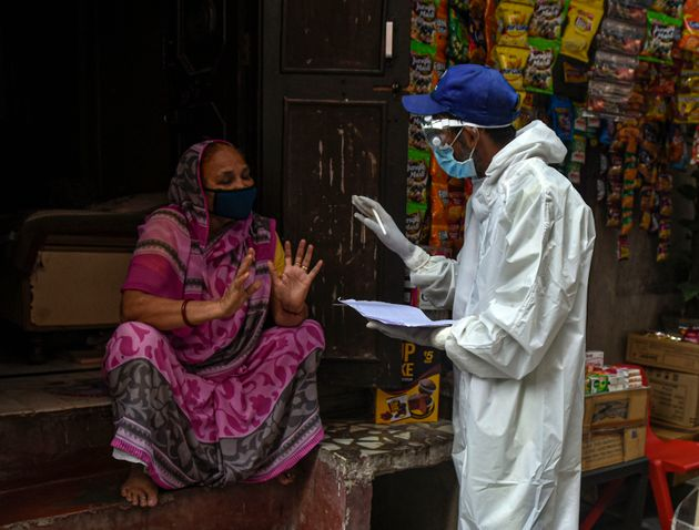 A health worker in PPE conducts a door to door screening survey for coronavirus in Karol Bagh's Ragarpura...