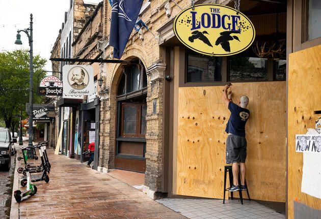 米テキサス州オースティンで26日、新型コロナウイルス対策で知事の営業停止命令を受け、バーの入り口に板を打ち付けるマネジャーの男性。地元紙オースティン・アメリカン・ステーツマン提供(AP)