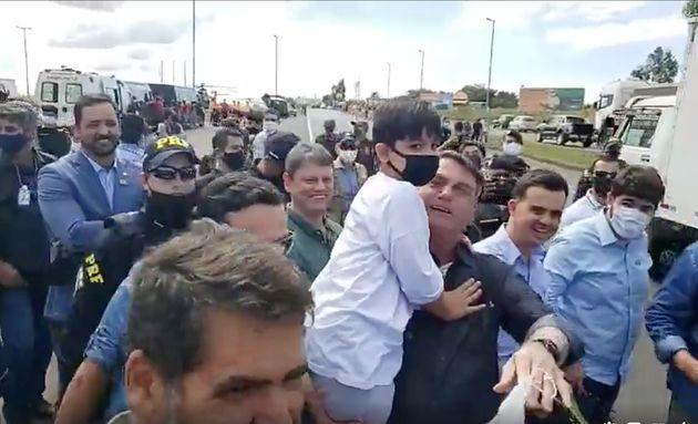 Sem máscara, Bolsonaro segura no colo criança que atravessou a