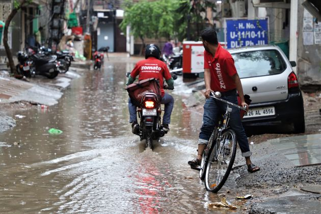 Zomato delivery boys move through water logged streets in Gurugram on the outskirts of New Delhi, India...