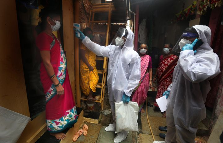 A health worker checks the body temperature of a resident, as others await their turn during a free medical checkup in a slum in Mumbai, India, Sunday, June 28, 2020. (AP Photo/Rafiq Maqbool)