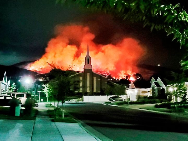 The Traverse fire burns behind homes in Lehi, Utah, early Sunday morning. Officials say fireworks caused the wildfire and for