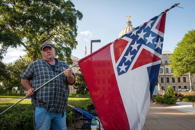 한 시위자가 미시시피 주 의사당 앞에서 주 깃발을 흔들고 있다. 잭슨, 미시시피주. 2020년