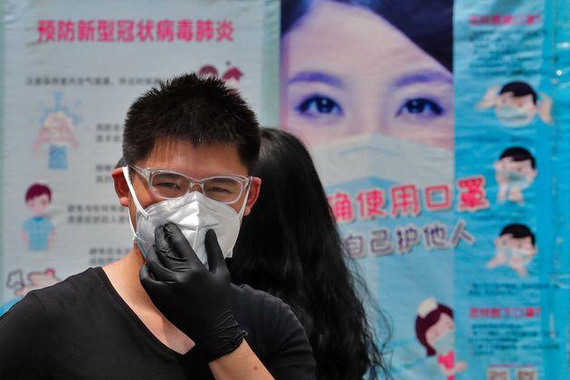 Un hombre ajusta su mascarilla el 28 de junio de 2020 en Pekín (AP Photo/Andy