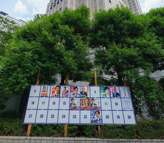 東京都知事選の候補者のポスター掲示場と都庁(6月20日撮影)。