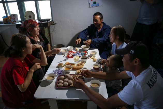 Gulnar Omirzakh, second right, and her husband, Baqytali Nur, third right, eat lunch with friends and...