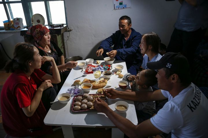 Gulnar Omirzakh, second right, and her husband, Baqytali Nur, third right, eat lunch with friends and family at their home in