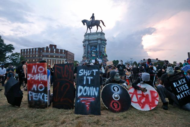 Protesters with shields and gas masks wait for police action as they surround the statue of Confederate...