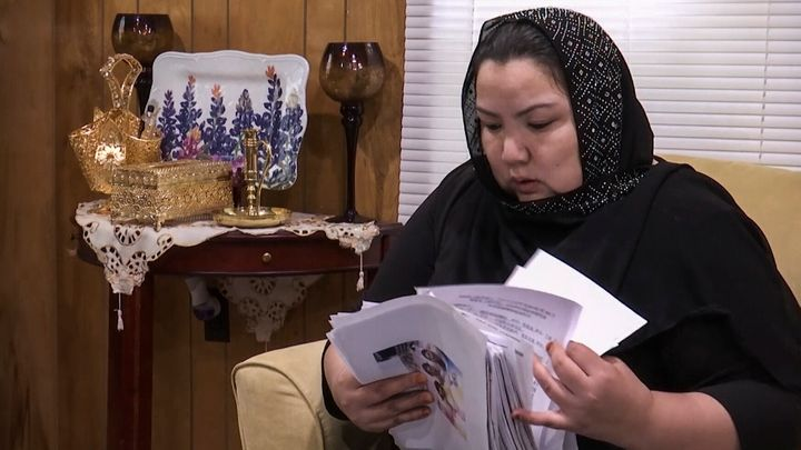 In this image from video, Zumret Dawut, a Uighur from China's far western Xinjiang region, holds documents she brought with h