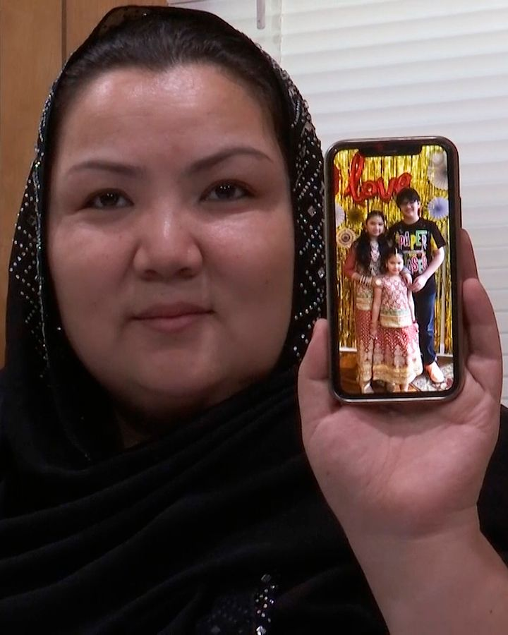 """In this image from video, Zumret Dawut, a Uighur woman from China's far western Xinjiang region, holds a phone with a picture of her kids at her home in Woodbridge, Va., on June 15, 2020. She says in China, a doctor tied her fallopian tubes. After waking from the anesthesia, she felt her womb ache, as though it was missing something. """"I was so angry. I wanted another son,"""" she said."""