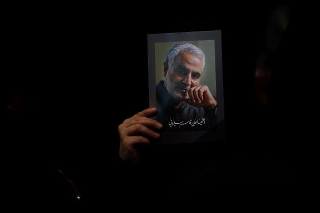 A Hezbollah supporter holds pictures of slain Iranian Revolutionary Guard Gen. Qassem Soleimani during...