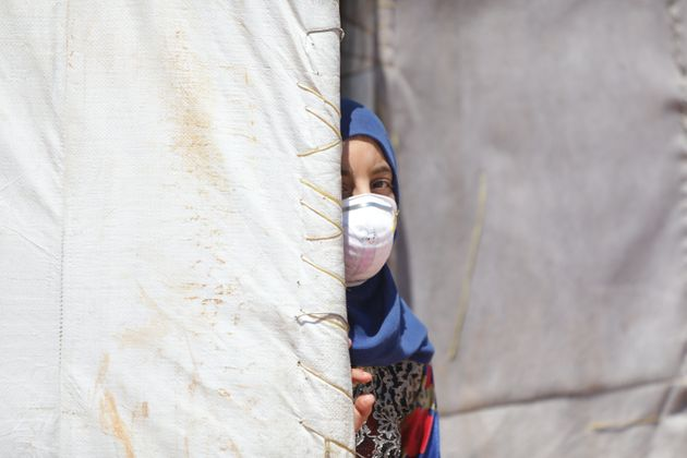 A Syrian girl wearing a medical mask is seen here at a refugee camp in Idlib, Syria, on June 19, 2020....