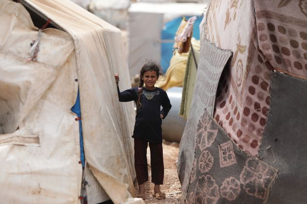 A young girl poses between tents at a refugee camp in Idlib, Syria, on June 19, 2020. Britain, Denmark,...