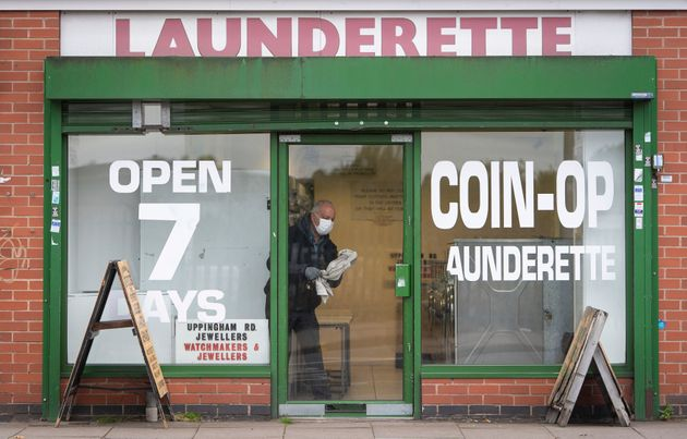 A man cleans the windows of a launderette in Leicester,