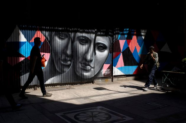 Pedestrian walk past a graffiti made by street artist Achilles in Athens, on Monday, June 3, 2019. (AP...