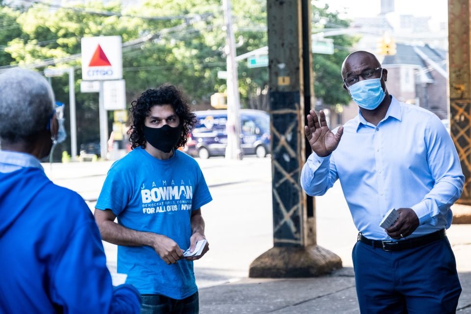 Jamaal Bowman, right, greets people outside a subway station in the Bronx. His presence in the district...