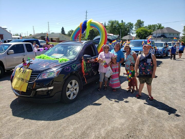 Participants in the Pride parade on June 27, 2020 pose with their bedazzled vehicle in Emo, Ont.