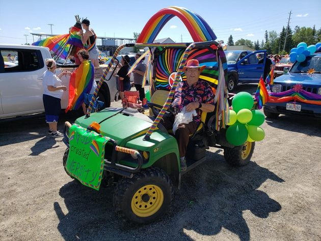 A participant in the Pride parade on June 27, 2020 poses with his decorated vehicle in Emo,