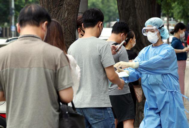 서울 여의도 성모병원에 마련된 선별진료소를 찾은 시민들에게 의료진이 문진표를 나눠주고 있다.