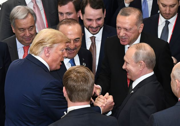 President Donald Trump shakes hands with Russian President Vladimir Putin as Turkey's President Recep...