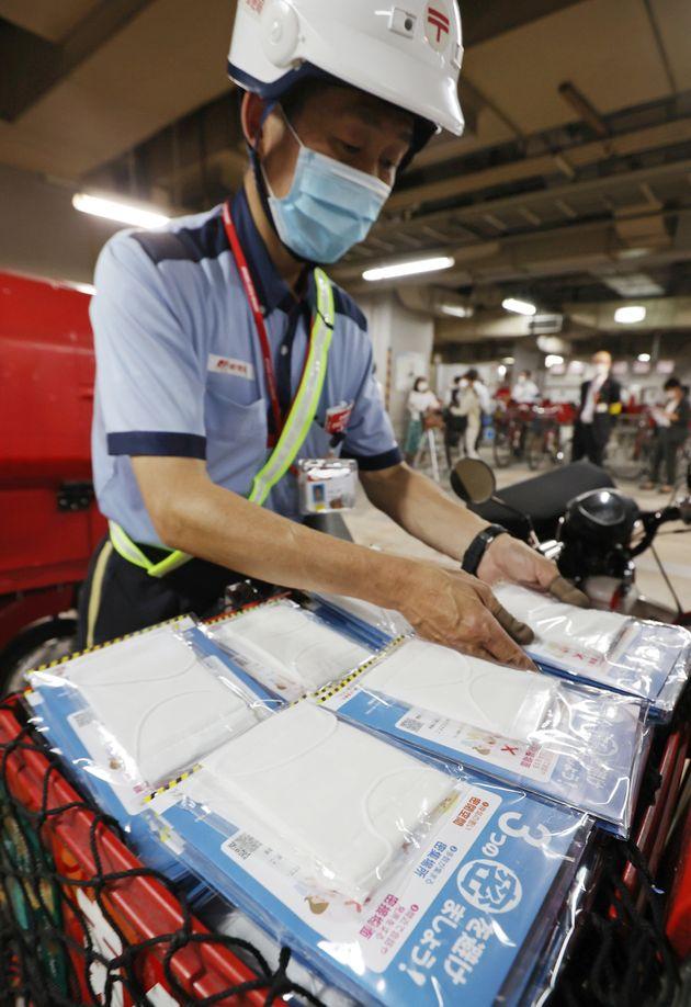 政府配布の布マスクをバイクに積み込む郵便局員