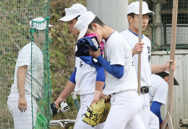 全国高校野球選手権大会の中止を伝えられ、タオルで顔を覆いグラウンドを出る大分・明豊の選手(中央)