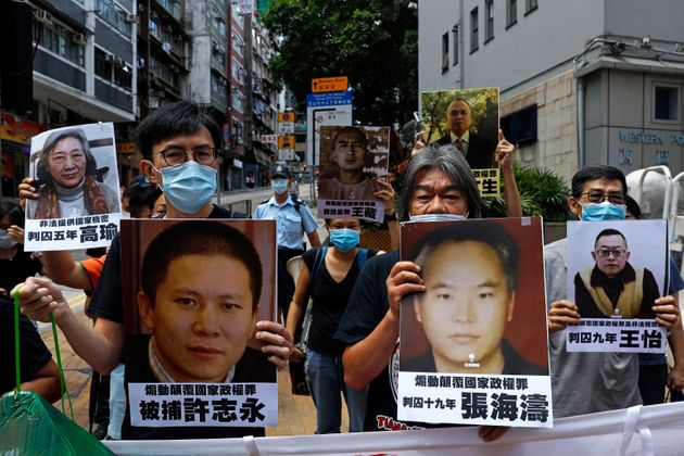 Pro-democracy demonstrators hold up portraits of jailed Chinese civil rights activists, lawyers and legal...