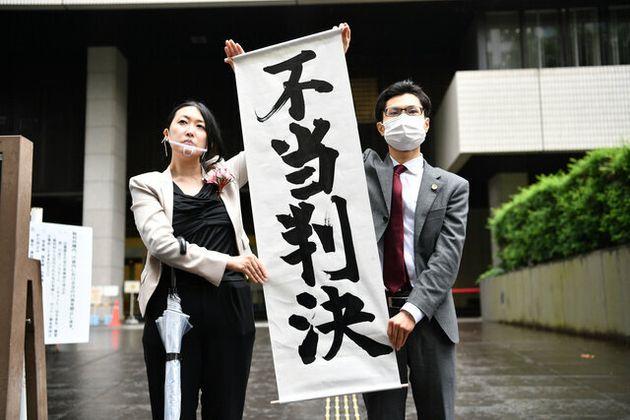 判決後、東京地裁前で「不当判決」の表示を掲げる原告側の弁護人=2020年6月30日午後2時14分、東京都千代田区、福留庸友撮影