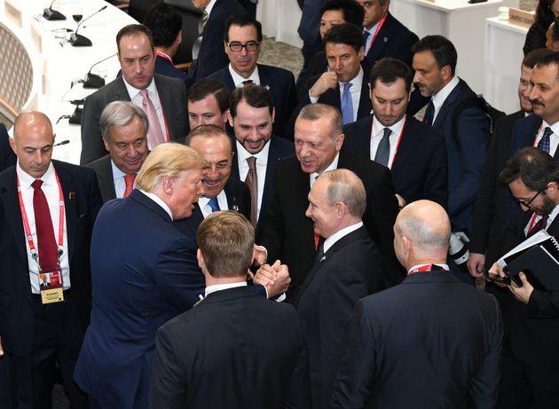 Donald Trump shakes hands with Russian President Vladimir Putin as Turkey's President Recep Tayyip Erdogan...