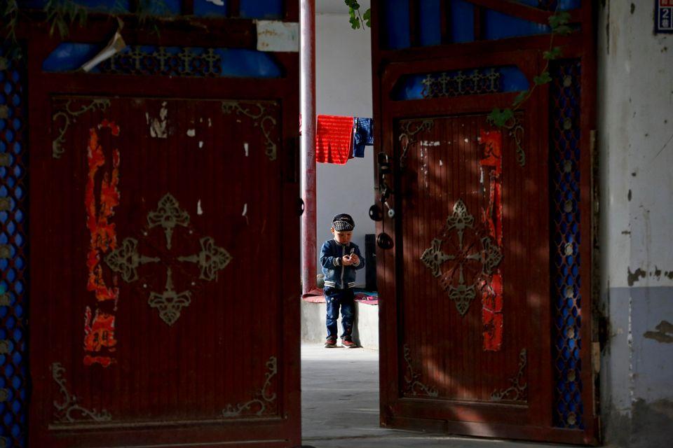 (자료사진) 허톈시, 신장 위구르 자치구, 중국. 2018년 9월20일 - 한 위구르 어린이가 집 앞마당에서 혼자 놀고 있다. 중국 정부는 소수민족에 대한 강제 산아제한 정책에 막대한...