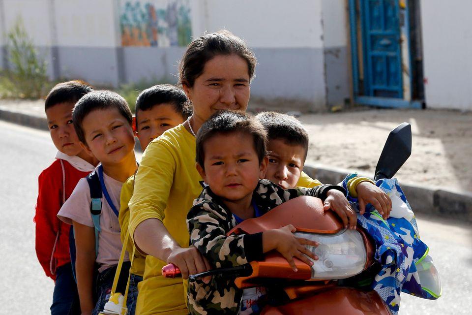 (자료사진) 허톈시, 신장 위구르 자치구, 중국. 2018년 9월20일 - 한 위구르 여성이 학교 수업을 마친 자녀들을 오토바이에 태우고 이동하고 있다. 정부 통계에 따르면 위구르...