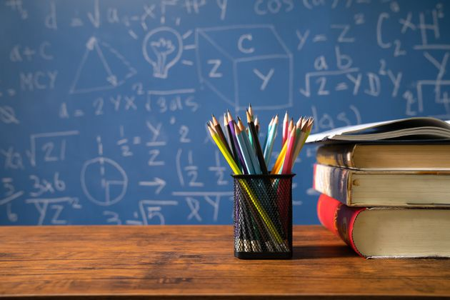 Back to school supplies. Books and blackboard on wooden