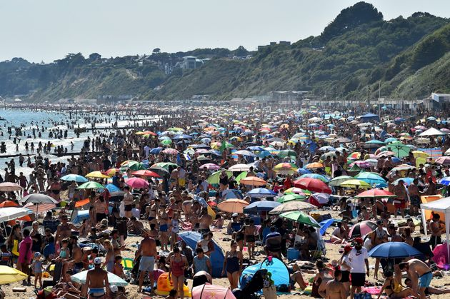 Beachgoers enjoy the sunshine as they sunbathe and swim on Bournemouth Beach in southern England on June