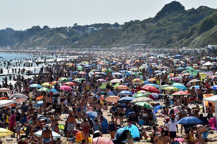 Beachgoers enjoy the sunshine as they sunbathe and swim on Bournemouth Beach in southern England on June 25.