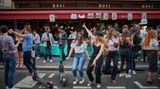 PARIS, FRANCE - JUNE 21: Parisians dance in the street at a bar in the 6th Arrondissement as Paris celebrates the first day of summer with Fete de La Musique with bands playing across the city on June 21, 2020 in Paris, France. Established in 1982 by the French Ministry of Culture to celebrate the diversity of musical genres in popular culture, Fete de la Musique is now celebrated throughout France and in over 120 countries around the world. This year due to the Covid-19 crisis most large concerts have been cancelled but the event is still embraced on a smaller scale in bars, cafes and street corners throughout the city. (Photo by Kiran Ridley/Getty Images)