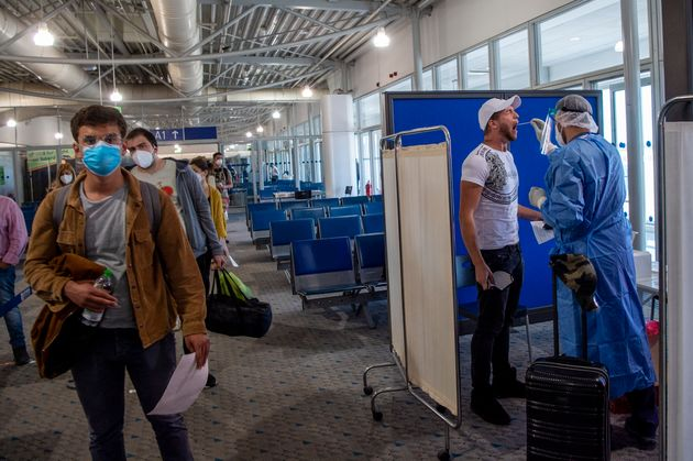 ATHENS, GREECE - JUNE 15: Medical staff conduct a test for the new coronavirus on the passengers who arrived from Doha to Eleftherios Venizelos International Airport in Athens on June 15, 2020 in Athens, Greece. The country removed most restrictions on travel from EU countries today in an effort to jumpstart its tourist season. Travelers from countries deemed high-risk, like the UK countries, will still face compulsory Covid-19 testing and mandatory quarantine. One week for a negative result; two weeks for a positive result. (Photo by Milos Bicanski/Getty Images)